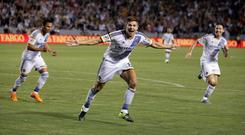 Los Angeles Galaxy's Steven Gerrard, center, of England, celebrates his first goal for the team, during the first half of an MLS soccer match against the San Jose Earthquakes, and celebrates with Robbie Keane (r)