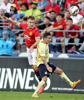 Manchester United's Luke Shaw (L) in action against Club America's Rubens Sambueza Action Images via Reuters / Anthony Bolante