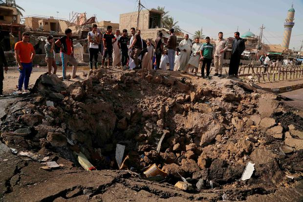 Civilians inspect a crater caused by a suicide car bombing at a busy market in Khan Bani Saad in the Diyala province Credit: AP Photo/Karim Kadim