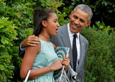 U.S. President Barack Obama walks out with his daughter Sasha from the White House in Washington before departure to New York July 17, 2015. President Obama and Sasha are traveling to New York City to meet up with Obama's other daughter Malia for some father-daughter time. REUTERS/Yuri Gripas