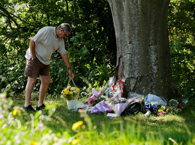 A man lays down flowers in tribute at the scene where motorist Donald Lock, who was a veteran member of the Worthing Excelsior Cycling Club, was stabbed and killed following a minor crash, in Findon, west Sussex. Yui Mok/PA Wire