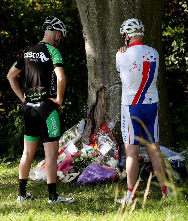 Cyclists look at floral tributes at the scene where motorist Donald Lock, who was a veteran member of the Worthing Excelsior Cycling Club, was stabbed and killed following a minor crash, in Findon, west Sussex. Yui Mok/PA Wire