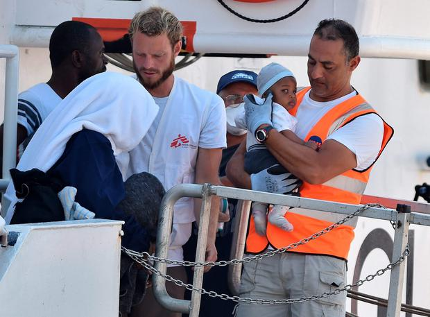 A volunteer holds a child who has just disembarked from the Migrant Offshore Aid Station (MOAS) vessel Phoenix, at the harbor of Messina, Sicily, Wednesday, July 15, 2015. (AP Photo/Carmelo Imbesi)