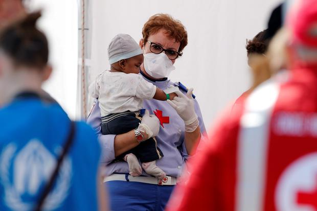 A Red Cross worker holds a baby after he was disembarked from the Migrant Offshore Aid Station (MOAS) ship MV Phoenix in the Sicilian harbour of Messina, Italy July 15, 2015. REUTERS/Antonio Parrinello