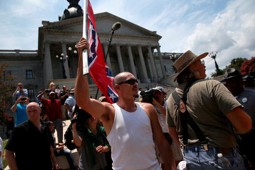 COLUMBIA, SC - JULY 18: A man holds a Confederate flag during a Black Educators for Justice rally at the South Carolina state house on July 18, 2015 in Columbia, South Carolina. The White Knights of the Ku Klux Klan were scheduled to hold a rally there afterwards, and police presence was heavy to prevent altercations between the two camps. (Photo by John Moore/Getty Images)