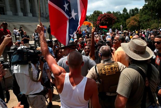 COLUMBIA, SC - JULY 18: A man holds a Confederate flag during a Black Educators for Justice rally at the South Carolina state house on July 18, 2015 in Columbia, South Carolina. The White Knights of the Ku Klux Klan were scheduled to hold a rally there afterwards, and the government issued a weapons ban around the state house as a precautionary measure. (Photo by John Moore/Getty Images)