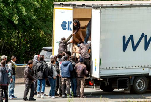 STRENGTH IN NUMBERS: Migrants climb in the back of a lorry on the A16 leading to the Eurotunnel in Calais, France