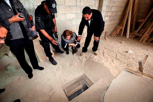 In this photo provided by Mexico's attorney general, authorities inspect the exit of the tunnel they claim was used by drug lord Joaquin