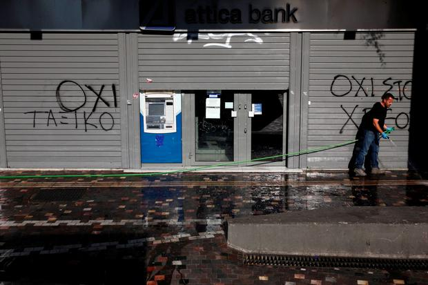 A man cleans the pavement in front a closed Attica Bank branch in Athens, Greece, July 19, 2015.The Greek government ordered banks to open on Monday, three weeks after they were shut down to prevent the system collapsing under a flood of withdrawals, as Prime Minister Alexis Tsipras looked to the start of new bailout talks next week.The graffiti reads,
