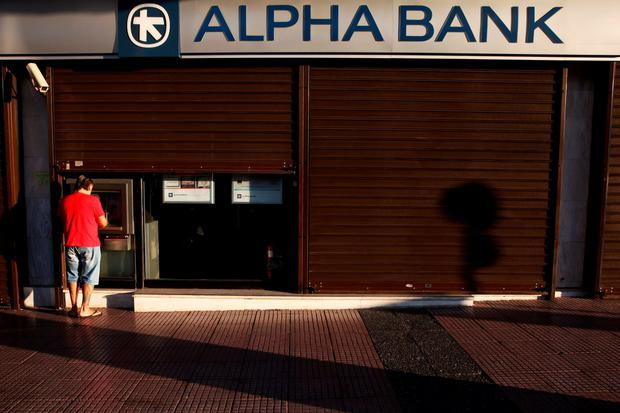 A man withdraws money at an Alpha Bank branch ATM in central Athens, Greece, July 19, 2015. The Greek government ordered banks to open on Monday, three weeks after they were shut down to prevent the system collapsing under a flood of withdrawals, as Prime Minister Alexis Tsipras looked to the start of new bailout talks next week. REUTERS/Yiannis Kourtoglou