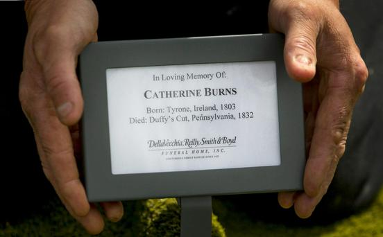 Gravedigger Laurence Devlin places a name plaque at the head of Catherine Burns' grave, after her funeral mass at Clonoe Chapel, Coalisland, after she was murdered in America 183 years ago and her remains lay buried in an unmarked grave for almost two centuries. PRESS ASSOCIATION Photo. Picture date: Sunday July 19, 2015. Catherine, 29, left County Tyrone for the United States in 1832 to begin a new life, but within six weeks she was dead. See PA story FUNERAL DuffysCut. Photo credit should read: Liam McBurney/PA Wire