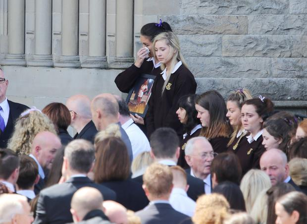 An emotional school firend holds up a photo of her late friend Tory Johnston Credit: North West Newspix