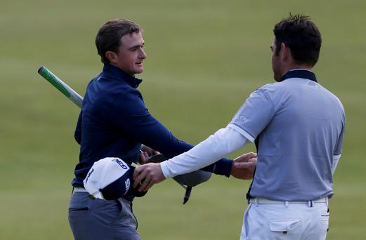 Paul Dunne of Ireland (L) shakes hands with Louis Oosthuizen of South Africa on the 18th green during the third round of the British Open golf championship on the Old Course in St. Andrews, Scotland, July 19, 2015. REUTERS/Russell Cheyne