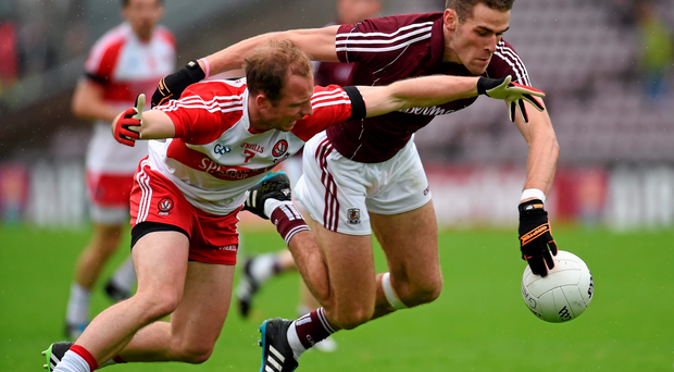 Galway's Fiontan O Curraoin squeezes out Derry's Sean Leo McGoldrick during Saturday's qualifier in Salthill, Co Galway