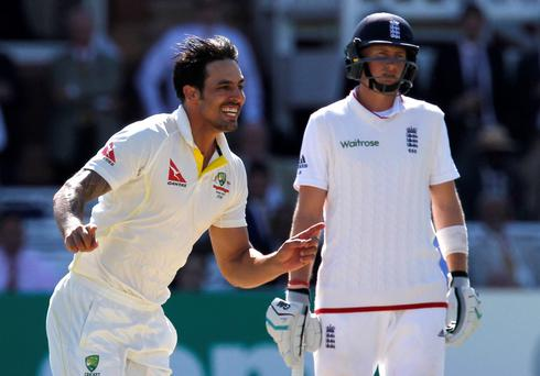 Mitchell Johnson celebrates an England wicket as Joe Root looks on