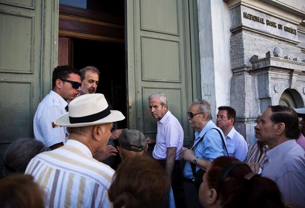 People wait to enter a National Bank branch in Athens, Greece July 20, 2015. Greeks queued outside banks on Monday as they reopened three weeks after closing to stop the system collapsing under a flood of withdrawals, the first cautious sign of a return to normal after a deal to start talks on a new package of bailout reforms. REUTERS/Ronen Zvulun