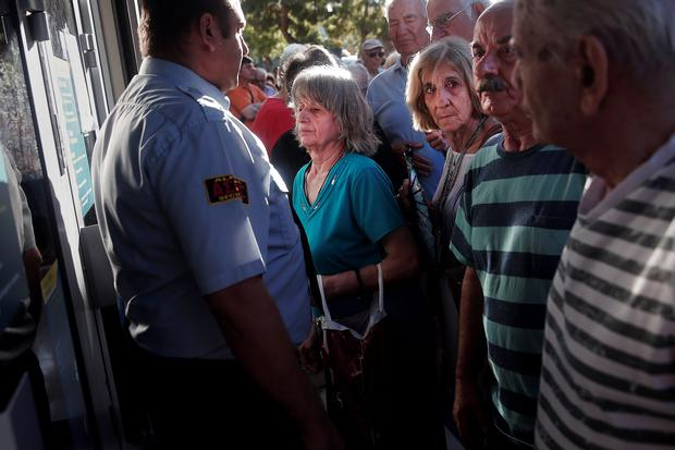 People line up outside a National Bank branch in Athens, Greece July 20, 2015. Greek banks opened their branches across the country on Monday after a three-week shutdown, officials said, while German Chancellor Angela Merkel called for swift aid talks so Athens could also lift withdrawal limits. REUTERS/Alkis Konstantinidis