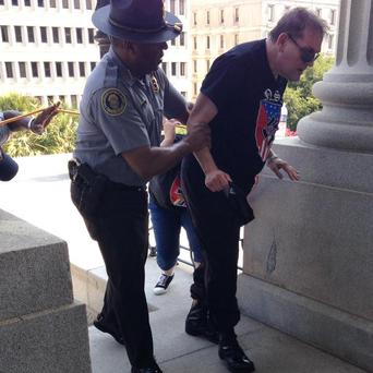 Officer Leroy Smith helping a heat-stricken man wearing a white supremacist shirt