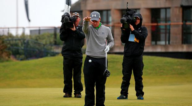Paul Dunne takes a drop after his ball ended up on the practice green on the second tee