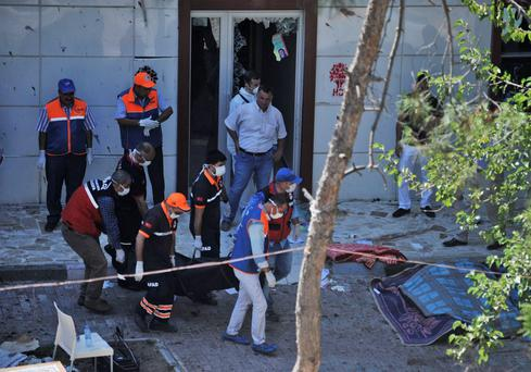 Medics carry out a body after an explosion in the southeastern Turkish town of Suruc, near the Syrian border, Monday, July 20, 2015. (AP Photo)