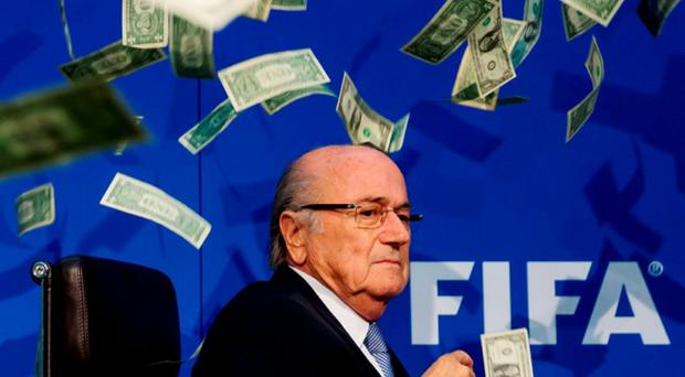 Sepp Blatter surrounded by banknotes thrown by British comedian Simon Brodkin during a press conference following the extraordinary FIFA executive committee meeting in Zurich