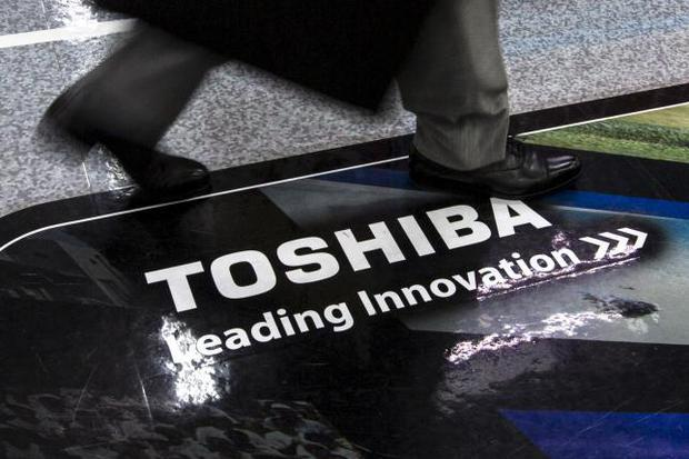 A man walks past a logo of Toshiba Corp at an electronics store in Tokyo July 21, 2015. REUTERS/Thomas Peter