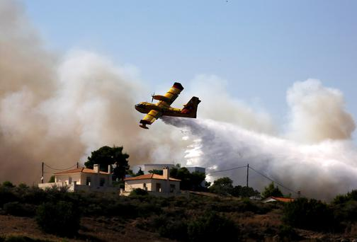 A firefighting plane drops water over a fire at holiday homes in Costa village in the Argolida region, in Southeastern Greece during a developing wild fire, July 20, 2015. Dozens of people were evacuated as firefighters fought the fire, which broke out on Monday afternoon in Panorama in Costa village at a forested area where dozens of summer houses are located, according to local media. REUTERS/Yannis Behrakis TPX IMAGES OF THE DAY