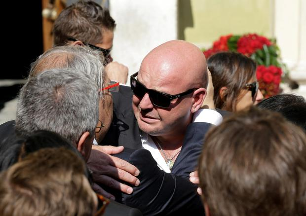 Philippe Bianchi, the father of French Formula One driver Jules Bianchi, is comforted by a relative prior to the funeral of his son at Sainte Reparate Cathedral in Nice, French Riviera, Tuesday, July 21, 2015. Bianchi, 25, died Friday from head injuries sustained in a crash at last year's Japanese Grand Prix. He had been in a coma since the Oct. 5 accident, in which he collided at high speed with a mobile crane which was being used to pick up another crashed car. (AP Photo/Lionel Cironneau)