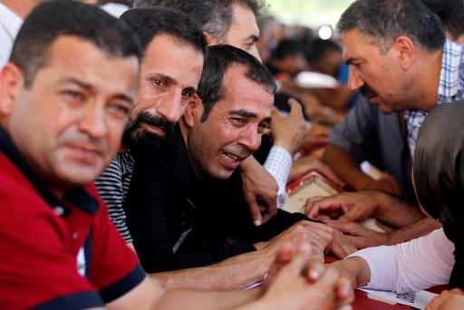 Relatives of victims who were killed in Monday's bomb attack in Suruc, mourn over the coffins at a cemetery in Gaziantep, Turkey, July 21, 2015. Photo: Reuters/Stringer