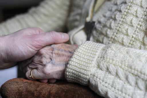 A woman, suffering from Alzheimer's desease, holds the hand of a relative