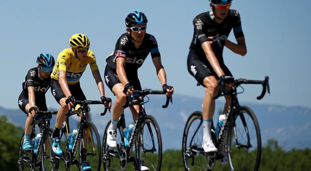 Team Sky rider Chris Froome , wearing the race leader's yellow jersey, cycles with team mates during the Tour de France
