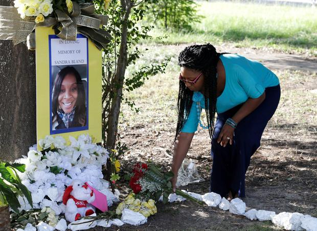 Jeanette Williams places a bouquet of roses at a memorial for Sandra Bland near Prairie View A&M University, Tuesday, July 21, 2015, in Prairie View, Texas. (AP Photo/Pat Sullivan)