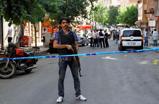 A plainclothes policeman stands guard following an attack on police officers in Diyarbakir, Turkey, July 23, 2015. REUTERS/Sertac Kayar