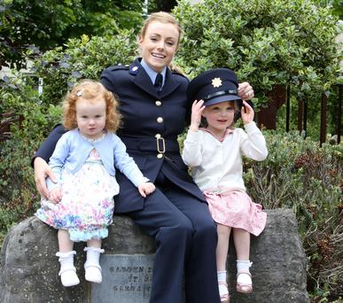 Garda Ciara Byrne from Lusk, who graduated yesterday from the Garda College in Templemore, enjoys the occasion with her daughters Lara (2) and Olivia (3)