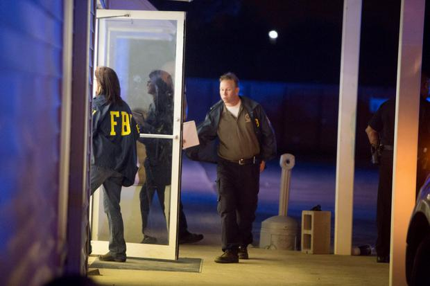 FBI officials enter a building near the movie theatre where a man opened fire on film goers in Lafayette, Louisiana July 23, 2015. A 58-year-old gunman opened fire inside a crowded movie theatre in Lafayette, Louisiana, on Thursday evening, killing two people and injuring seven others before taking his own life, police said. REUTERS/Lee Celano