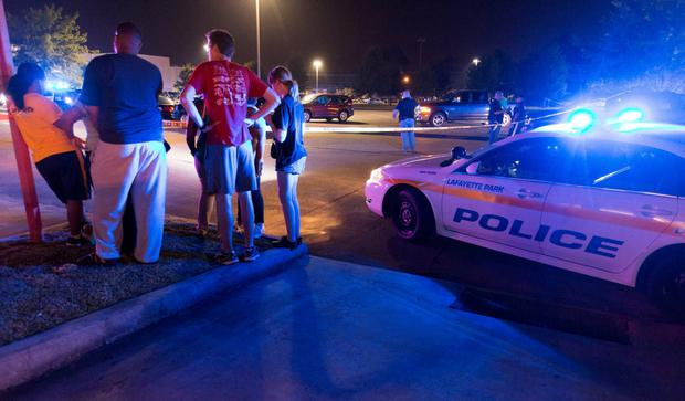 Bystanders watch over the scene at a movie theatre where a man opened fire on film goers in Lafayette, Louisiana