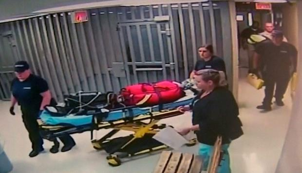 Medics leave with equipment on a stretcher at Waller County Jail in Hempstead, Texas