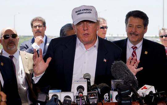 Republican presidential candidate Donald Trump gestures during a news conference near the U.S.-Mexico border (background), outside of Laredo, Texas July 23, 2015. At right is Pete Saenz, mayor of Laredo. REUTERS/Rick Wilking