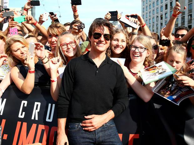 Actor Tom Cruise poses with fans as he attends the world premiere of 'Mission: Impossible - Rogue Nation' at the Opera House (Wiener Staatsoper) on July 23, 2015 in Vienna, Austria. (Photo by Andreas Rentz/Getty Images for Paramount Pictures International)