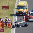 Force India driver Sergio Perez of Mexico, green helmet, stands next to his overturned car during the first practice session for the Formula One Hungarian Grand Prix on the Hungaroring circuit in Mogyorod, 23 kms north-east of Budapest, Hungary, Friday, July 24, 2015. The 2015 Formula One Grand Prix of Hungary will take place on July 26. (Zsolt Czegledi/MTI via AP)