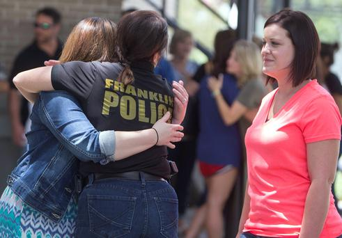 Franklyn Police Chief Sabria McGuire hugs Christian Wise as Britney Landry looks on outside a rosary service for Mayci Breaux in Franklin, Louisiana July 24, 2015. An Alabama drifter opened fire inside the crowded movie theater in Lafayette, Louisiana Thursday night killing Breaux and Jillian Johnson, police said, in the latest act of random gun violence to shock the United States. REUTERS/Lee Celano