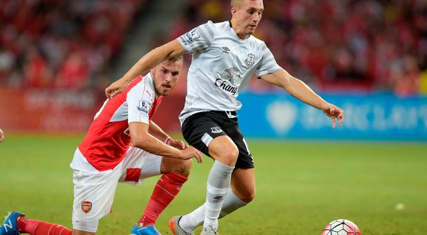 Everton's James McCarthy, right, vies for the ball with Arsenal's Aaron Ramsey during their soccer match for the Asia Trophy in Singapore, Saturday, July 18 (AP Photo/Joseph Nair)