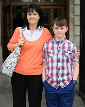 Adam Tiernan from Clondalkin, with his mum, Angelaine outside the Four Courts yesterday