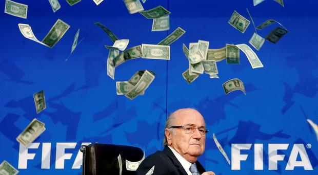 FIFA President Sepp Blatter reacts to banknotes thrown at him by a British comedian earlier this week, as the embattled organisation admitted it was struggling to attract new sponsors and was heavily criticised by the chief executive of Visa, a key commercial partner