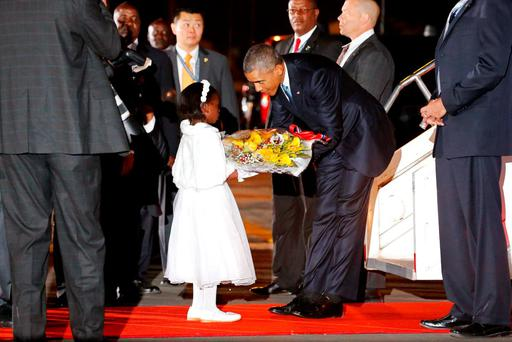US President Barack Obama receives flowers from a girl as he arrives aboard Air Force One at Jomo Kenyatta International Airport in Nairobi. Photo: Reuters