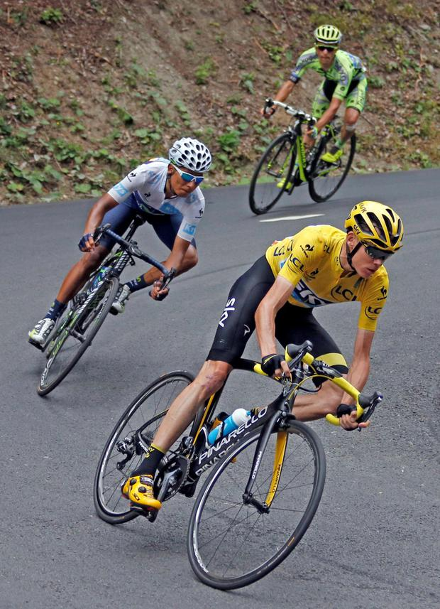 Team Sky rider Chris Froome (r), the race overall leader's yellow jersey, speeds downhill followed by Movistar rider Nairo Quintana (c) and Tinkoff-Saxo rider Alberto Contador (top) in the Glandon pass during the 138-km 19th stage of the 102nd Tour de France