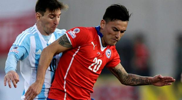 Chile's Charles Aranguiz (20) is tackled by Argentina's Lionel Messi during their Copa America final