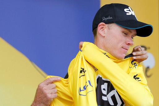 Britain's Chris Froome puts on the overall leader's yellow jersey on the podium of the nineteenth stage of the Tour de France
