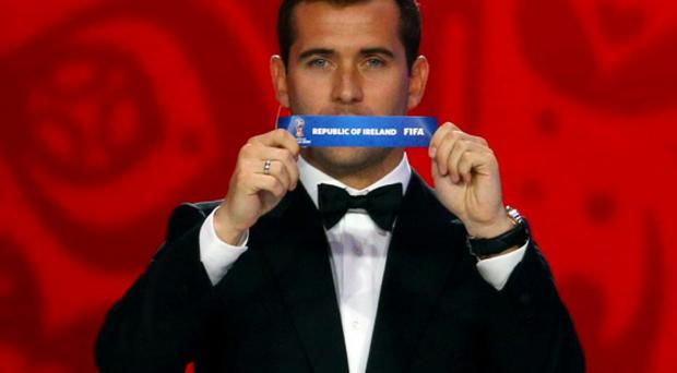 Former Russian soccer player Aleksandr Kerzhakov holds up the slip showing