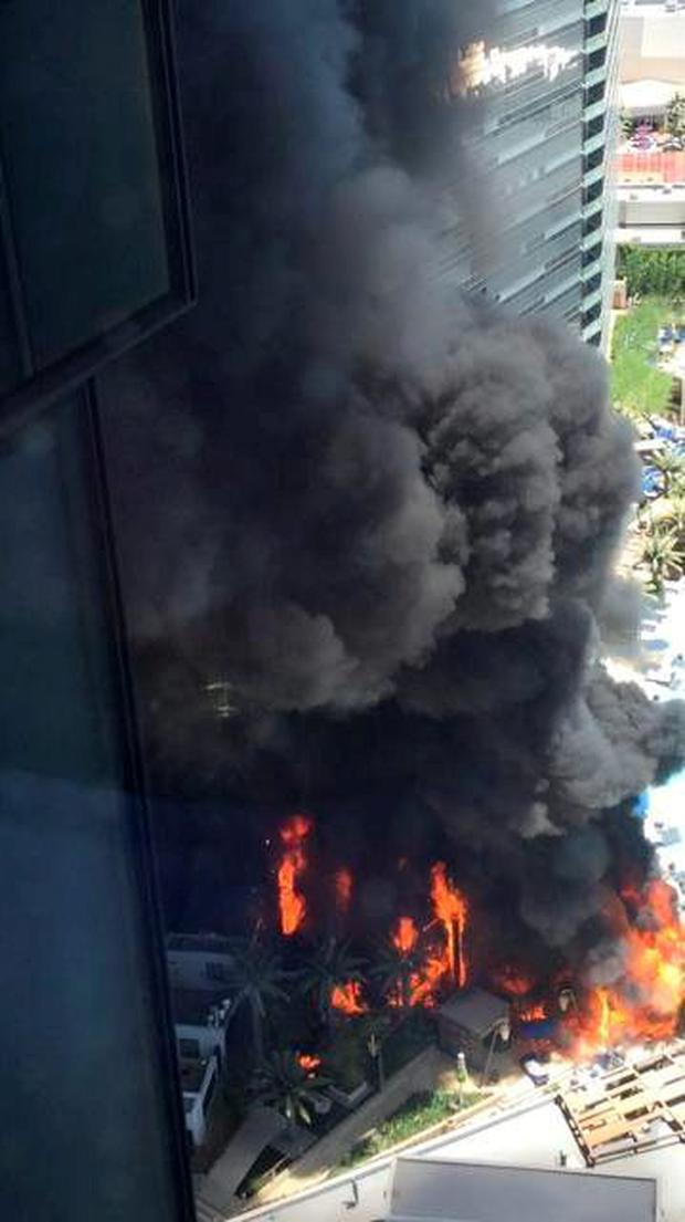 In this photo provided by Julio Loredo, smokes billows from a fire on the outside pool area of the Cosmopolitan Las Vegas hotel-casino (Julio Loredo via AP)